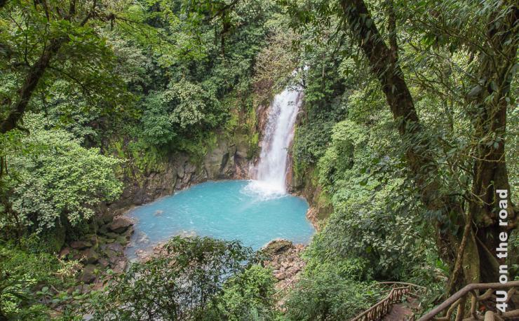Bild zeigt den milchig blauen Wasserfall umgeben von grünem Dschungel und die steile Treppe abwärts.