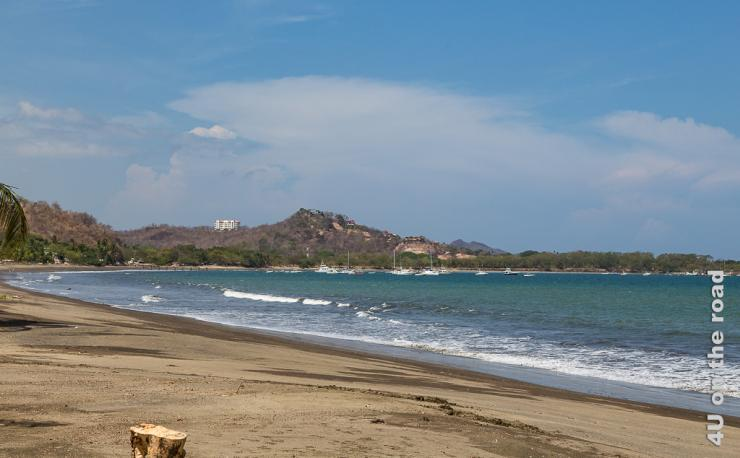 Bild zeigt Strand, Meer, Yachthafen und einen bebauten Hügel im Hintergrund.