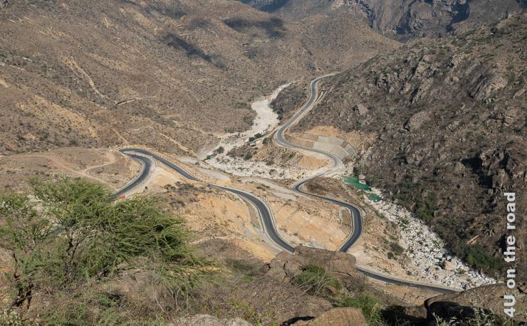 Strasse R 47 schraubt sich in einen Canyon hinunter, Reste grünen Wasser stehen noch im Wadi. Überall werden die Hänge befestigt.