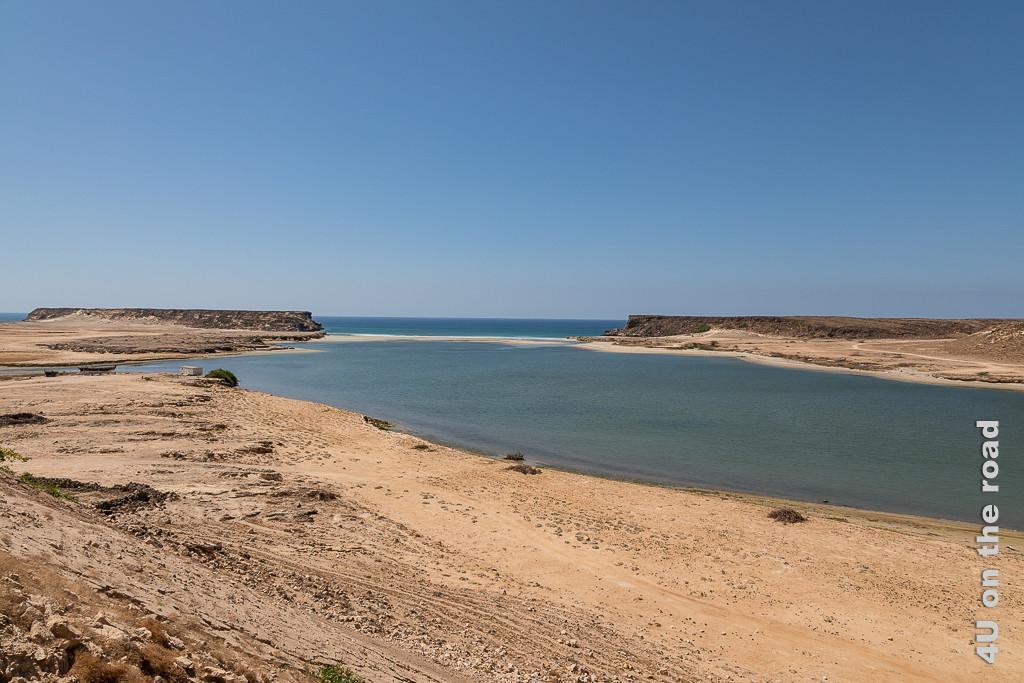 Bild Khor Rori zeigt den Meeresarm, der von einer schmalen Sandbank vom Meer getrennt ist. Rechts und Links neben der Sandbank stehen Felsplateaus.