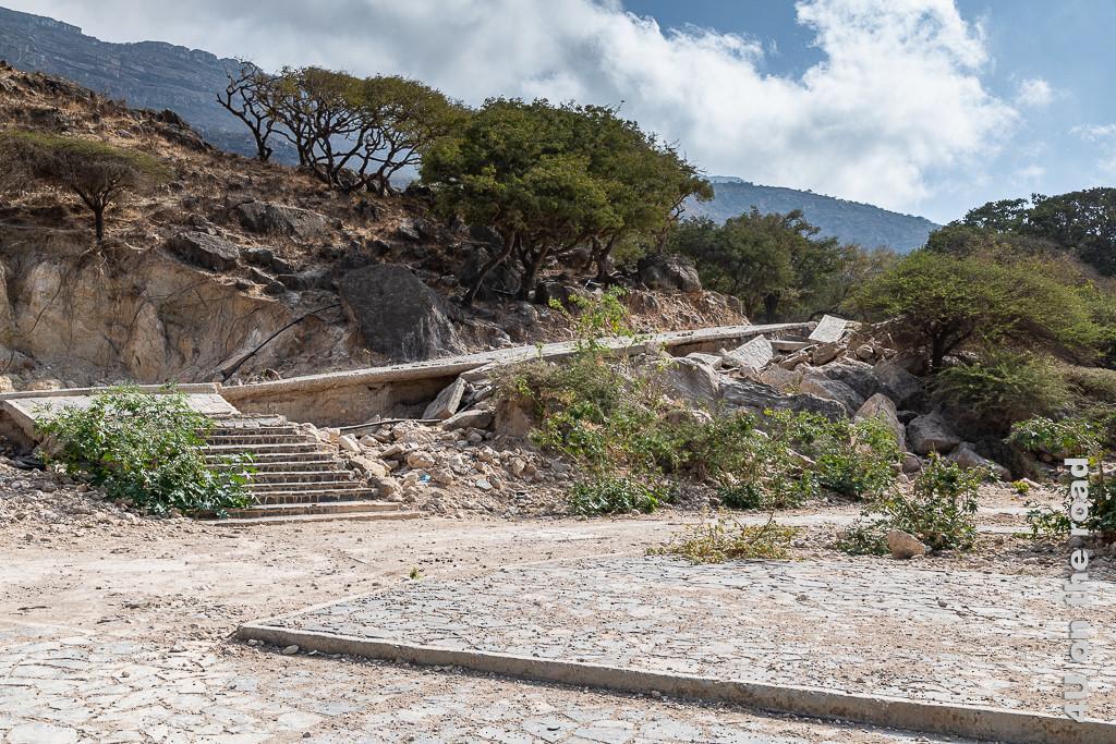 Bild Unterspülte Strasse auf dem Weg zur Quelle zeigt eine Strasse im felsigen Hang, welche teilweise zerbrochen und teilweise unterspült ist. Grüne Bäume und Sträucher wachsen in den Felsen neben der Strasse.