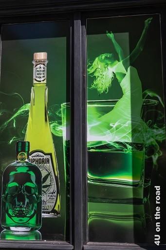 Bild Werbung für die grüne Fee in der Prager Innenstadt zeigt ein Schaufenster mit einer Flasche mit grünem Totenkopf, einer grösseren hellgrüneren Flasche dahinter und einer tanzenden grünen Fee im Glas.