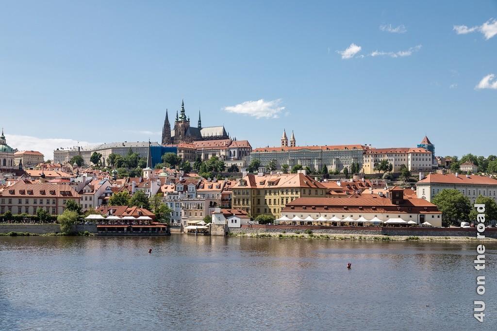 Bild Hradschin von der gegenüberliegenden Seite aus gesehen, zeigt die Moldau und die sich dahinter erhebende Burganlage, die vom St. Veiths Dom überragt wird.