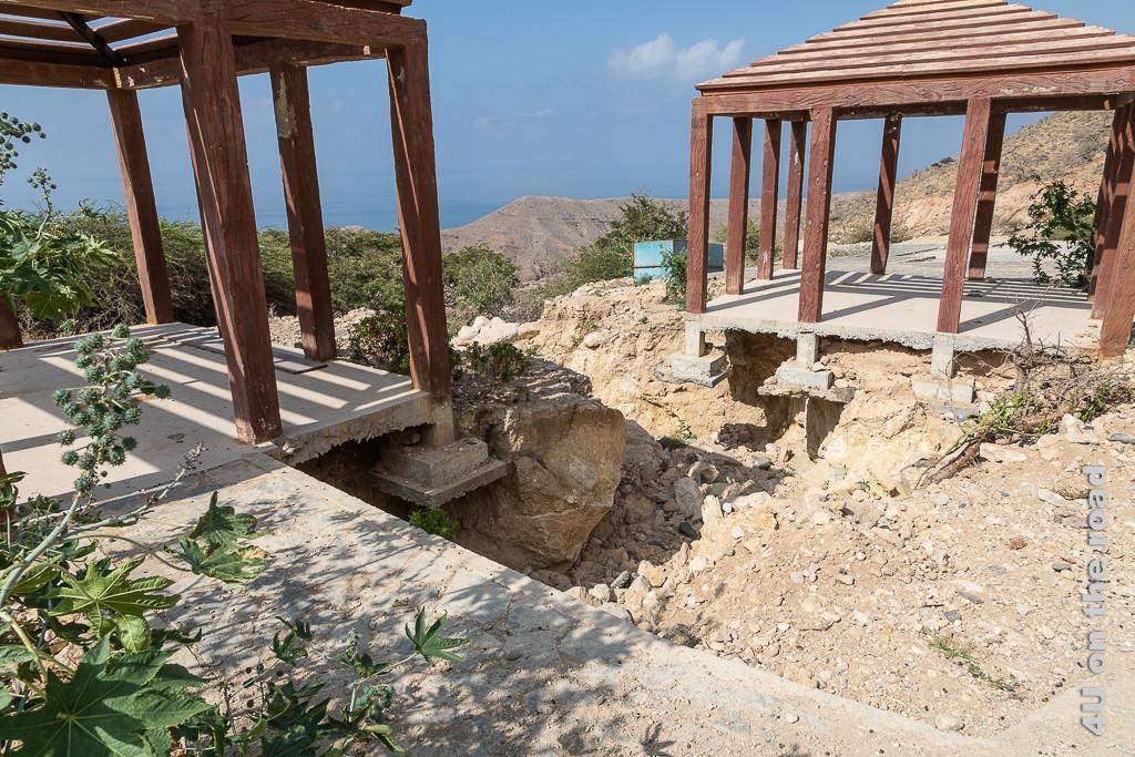 Bild Pavillons völlig losgelöst von der Erde zeigt zwei Pavillons, deren Stützpfeiler auf der einen Seite komplett mit den Betonfundamenten in der Luft hängen. Dahinter sieht man die Küste durchschimmern.