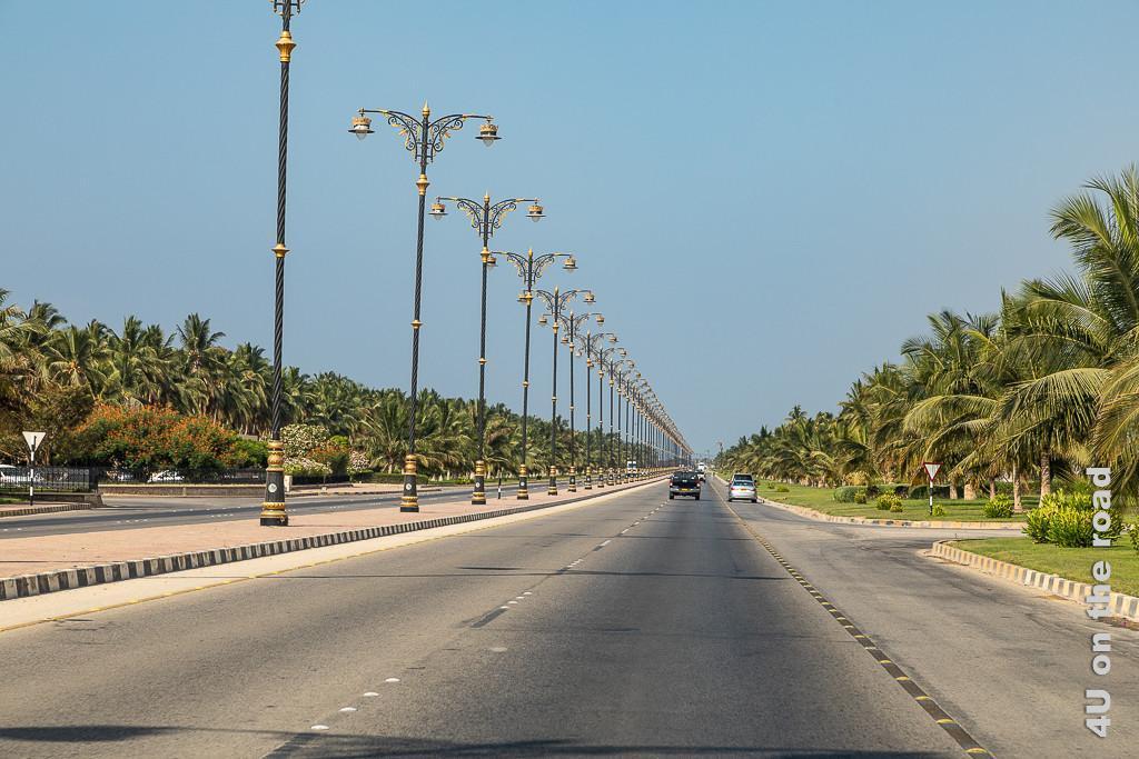 Bild Wenig Verkehr auf der Strasse - Salalah, zeigt eine Prachtstrasse, welche rechts und links von Palmen und Rasenflächen gesäumt ist. Die zwei Mal dreispurige Strasse ist durch einen Mittelstreifen getrennt, auf dem alls 30 Meter blau-goldene Laternen stehen.