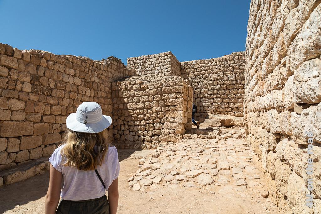 Bild Dicke Mauern- Sumhuram zeigt die Mauern nach dem Eingangstor. Im Vordergrund die Rückansicht von Morgaine mit langen Haaren und weissem Hut.