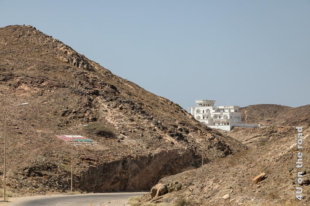 Dild Abfahrt nach Sadah zeigt die tief in die Felsen eingeschnittene Strasse. Im Hintergrund drohnt eine weisse Villa auf den braunen Felsen.