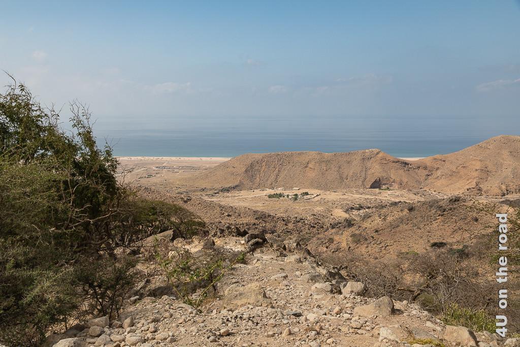 Bild Blick auf die Küste zeigt die trockene und karge Landschaft zwischen dem Küstengebirge und dem Meer. Nur vereinzelt bei Gehöften sind grüne Büsche sichtbar.