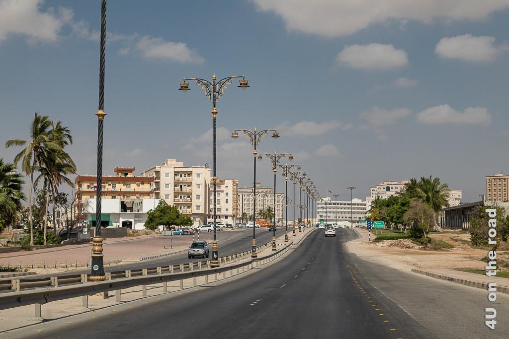 Bild Salalah - Wohnblocks entlang der Strasse zeigt eine vierspurige Strasse mit blau-goldenen Laternen. Rechts und Links stehen moderne, orientalische und auf ältere Wohnblocks.