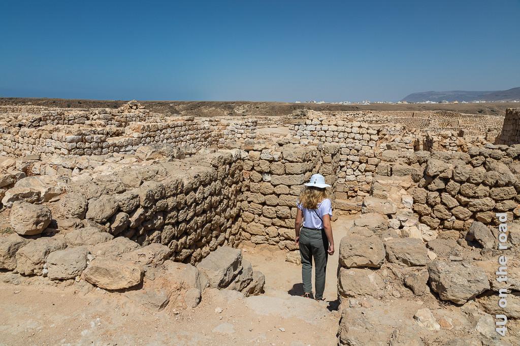 Bild In den Mauern der Stadt Sumhuram unterwegs zeigt im Vordergrund Mauerreste von Häusern mit Treppen und wegen, Morgaine mit weissem Hut und offenem Haar von hinten. In der Ferne sieht man die Häuser der Stadt Taqa.