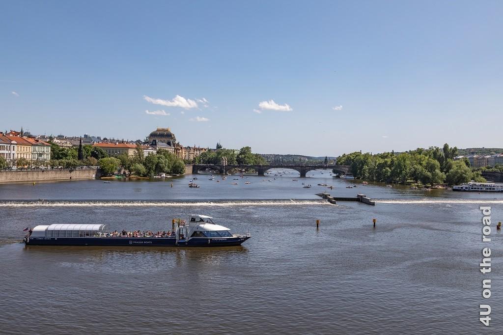 Bild Blick von der Karlsbrücke in Richtung - most Legií - Prag zeigt im Vordergrund ein an der Staustufe wendendes Ausflugsschiff, Strelecký Island, viele kleine Boote vor und hinter der Brücke, sowie die Häuser, die den Uferrand säumen.