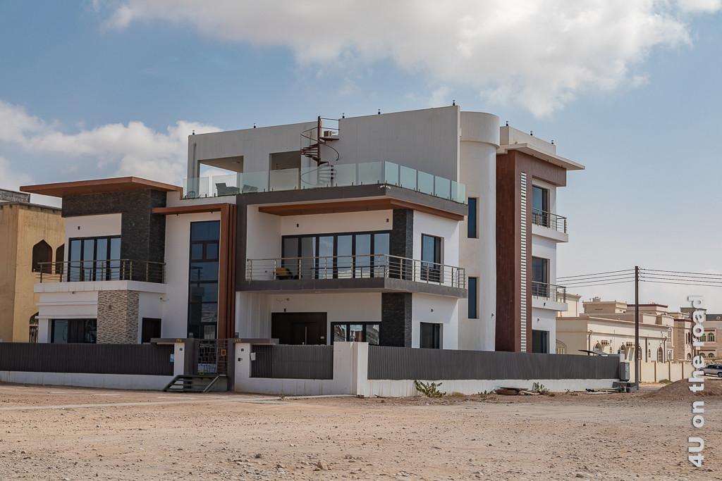 Bild Salalah- selten sieht man europäische Architektur zeigt ein grosses, moderenes von einer Mauer Umgebenes Privathaus mit drei Etagen und mehreren Terrassen, u.a. einer Dachterasse