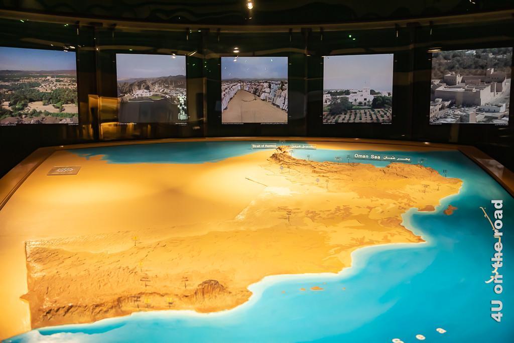 Bild Relief des Omans im Museum of Frankincense Land zeigt im Vordergrund ein grosses Relief des Wüstenstaates. Im Hintergrund zeigen beleuchtete Bilder an der Wand Facetten des Landes.