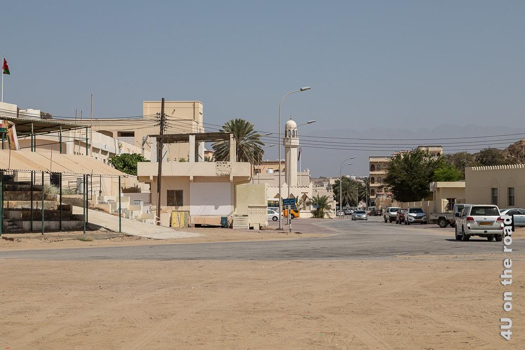 Bild Blick vom Hafen in Richtung Ort Sadah zeigt den beigefarbenen Ort mit Häusern, Moschee und Fahrzeugen. Der Ort ist erstaunlich grün. Überall wachsen grosse Palmen und Bäume.