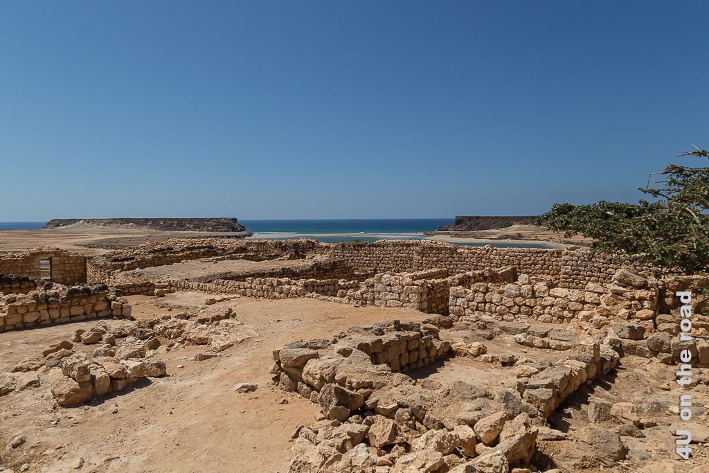 Bild Blick von Sumhuram aufs Meer zeigt den Blick aufs Meer, die Sandbank und die beiden Plateaus über die Mauern und Durchgänge der Stadt