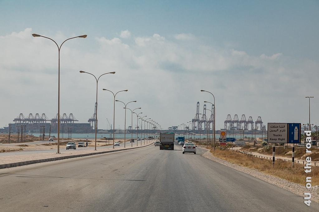 Bild Blick auf den Hafen - Salalah zeigt sechsspurige Strasse zum Hafen. Im Hintergrund erheben sich die Hafenkräne am Wasser.