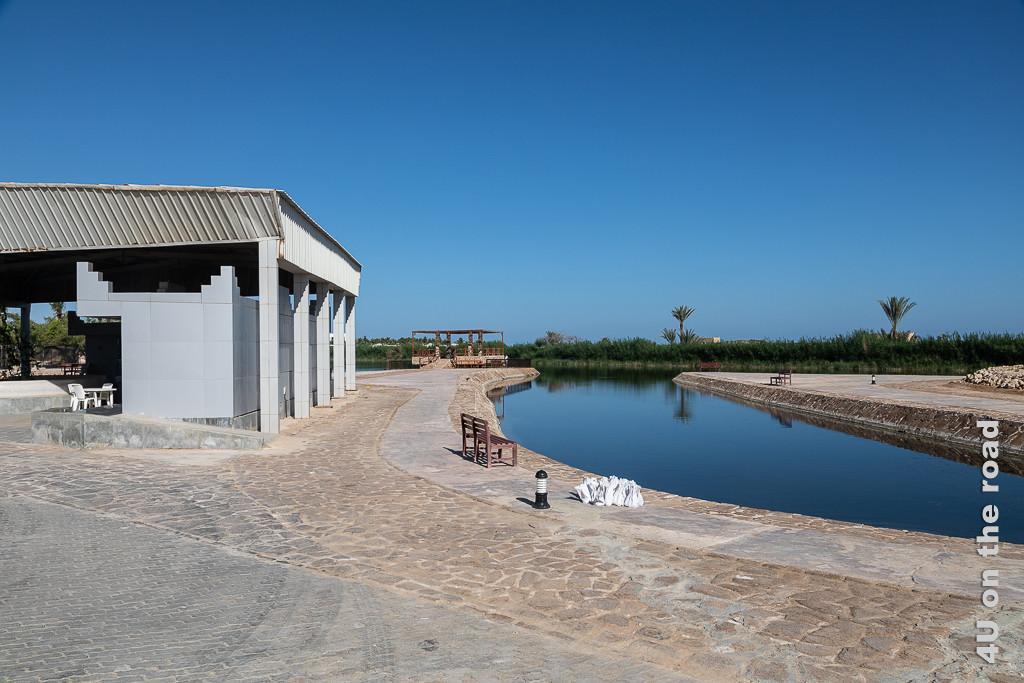Bild Café und Visitor Center an der Lagune zeigt das Gebäude und den schön mit Steinen eingefassten Kanal der Lagune mit Bänken und Picknickplätzen. Im Hintergrund stehen Büsche und Palmen.