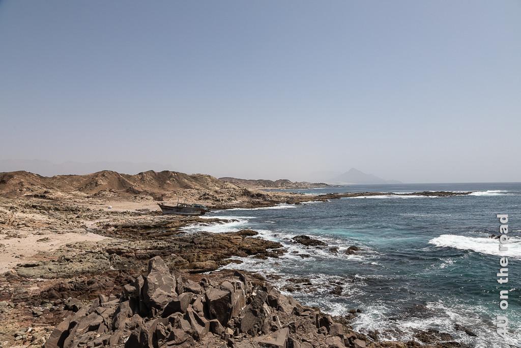 Bild Küste mit Wrack hinter Sadah zeigt das schäumende Meer, spitze Felsen, ein grosses Schiffswrack an Land. Im Hintergrund erhebt sich ein spitzer Berg im Dunst.