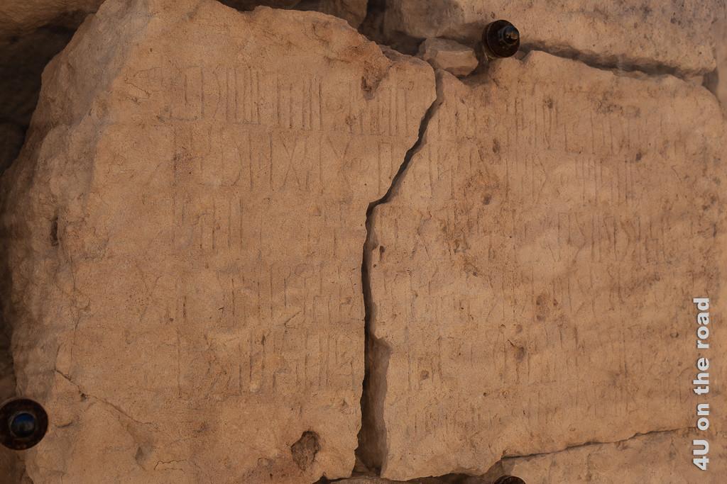Bild Steintafel, die Auskunft über die Stadtgründung und den Namen der Stadt - Sumhuram gibt zeigt die in der Mitte gerissene Steintafel mit Schriftzeichen, die aussehen wie eine Mischung aus Hieroglyphen und Griechisch.