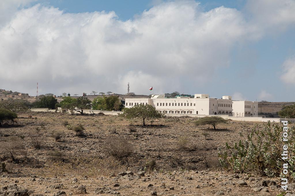 Bild Schule Tawir Attir zeigt ein fast weisses Gebäude, welches im starken Kontrast zur kargen Landschaft steht. Das Gebäude erinnert vom Baustil an ein Regierungsgebäude. Im ummauerten Pausenhof stehen grosse, grüne Bäume. Zwei Mobilfonantennen sind im Hintergrund zu erkennen.