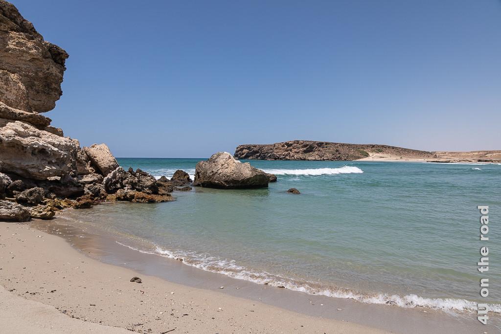 Bild Sumhuram - Meeresbucht zeigt von links in die Mitte des Bildes fallende Felsen, Wellen die in die Buch strömen und die gegenüberliegende Seite der Bucht bestehend aus Felsen und Sand