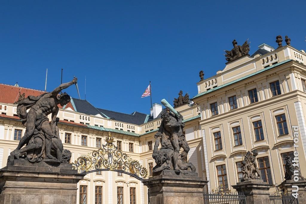 Bild Der Ehrenhof, Prager Burg zeigt die Skulpturen, welches das Tor bewachen. Eine Figur holt mit einer Keule aus und zielt auf einen liegenden Mann, die andere Figur ist mit einem Dolch in einer stechenden Bewegung auf den unter ihr liegenden Mann dargestellt.