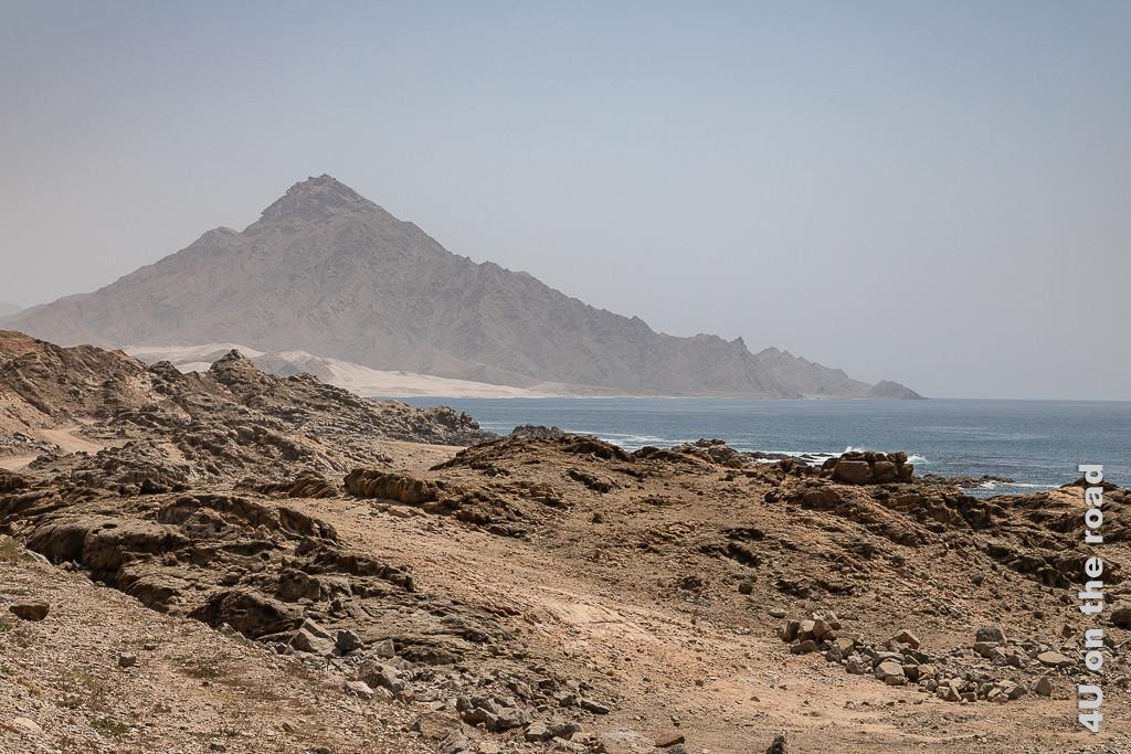 Bild Sandige Abschnitte zwischen den Felsen zeigt Bucht mit feinstem Sandstrand bevor sich ein scharfkanntiger spitzer Berg aus dem Wasser erhebt.
