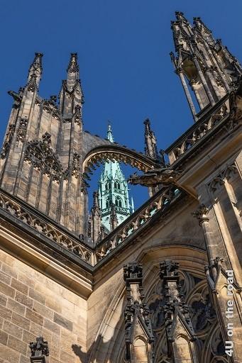 Bild Impression St. Veits Dom zeigt Sandstein Spitzen und Rundbogen hinter dem ein kupfergrüner Turm herausschaut.