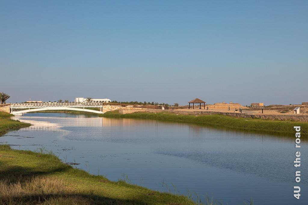 Bild Im Golfwagen geht es in rasanter Fahrt entlang der Lagune im Al Baleed Ausgrabungsgelände zeigt die Lagune mit Brücke und erste Teile der Ausgrabung