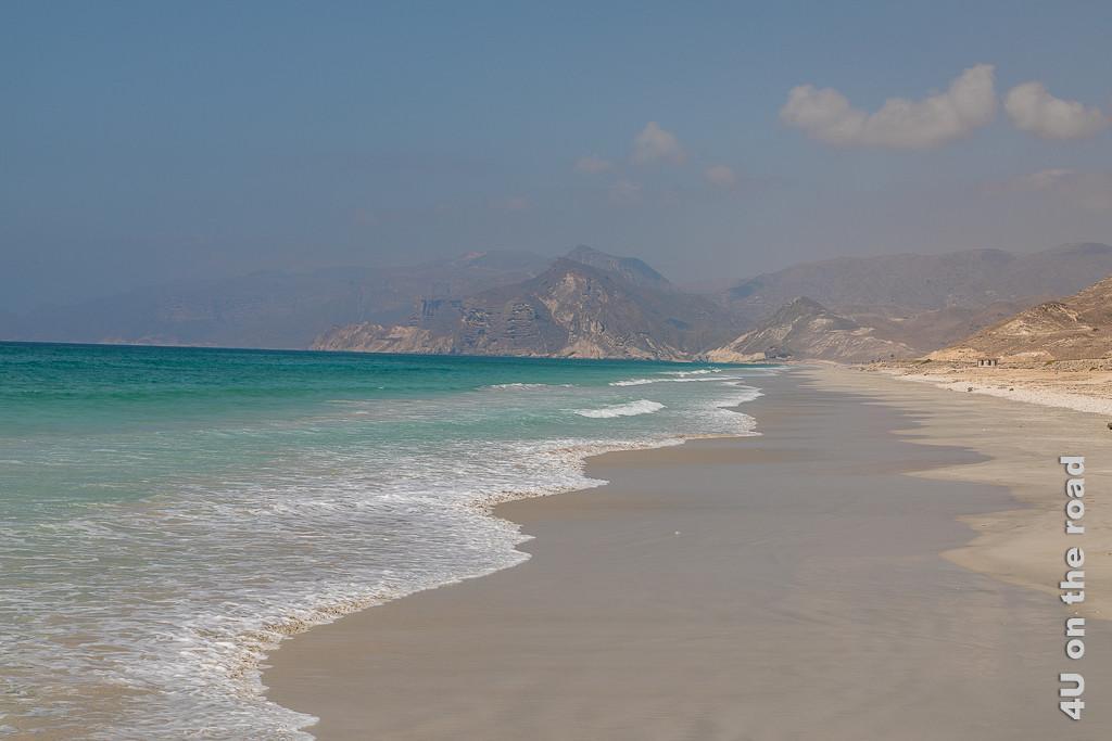 Bild Mughsail Beach, Oman zeigt den sich endlos bis zu den Klippen im Hintergrund erstreckenden, menschenleeren Sandstrand.