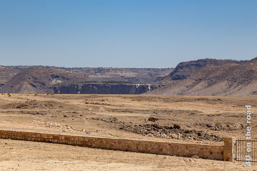 Wasserfall vom Wadi Darbat von Sumhuram aus gesehen zeigt im Hintergrund eine erhöhte Ebene zwischen zwei Bergen mit einer steilen Abbruchkante, über die rechts noch Wasser stürzt. Auf der Ebene wachsen Palmen, der Rest der landschaft ist felsig.