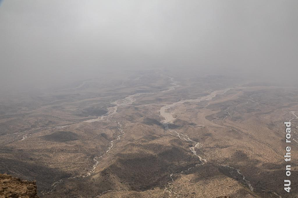 Das Bild Wolkenfetzen verhindern die Sicht zeigt die Aussicht vom Jebel Samhan Aussichtspunkt auf die Küste, welche aber in den Wolken nicht zu erkennen ist. Dafür sieht man die Spuren vieler kleiner Flüsse vom Berg, die sich am Fuss zu grossen, mäandernden Wadis auswachsen.