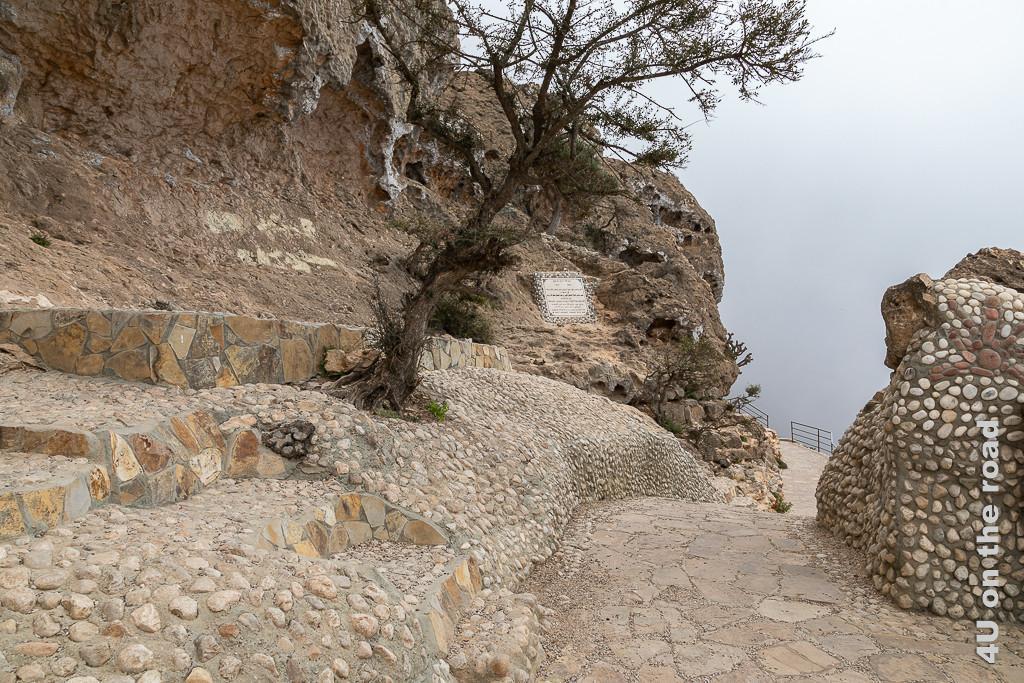 Bild Auf dem Weg zur Aussicht auf den Jebel Samhan zeigt den mit kleinen Steinen als Terrassen befestigten Hang mit windschiefen Baum. Dahinter ragt ein Felsen mit Gedenktafel auf. Der Weg fürht scheinbar ins Nichts, denn nach den Geländern sieht man nur noch die Wolken