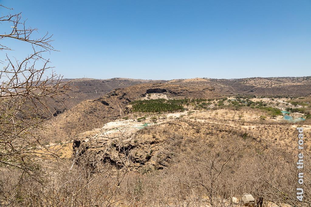 BIld Blick auf den Wasserfall und Wadi Darbat zeigt die Abbruchkannte des Plateaus von der Seite und zeigt die Ebene durch die sich das Wadi mit türkisem Wasser zieht. Die Ebene ist grün bewachsen.