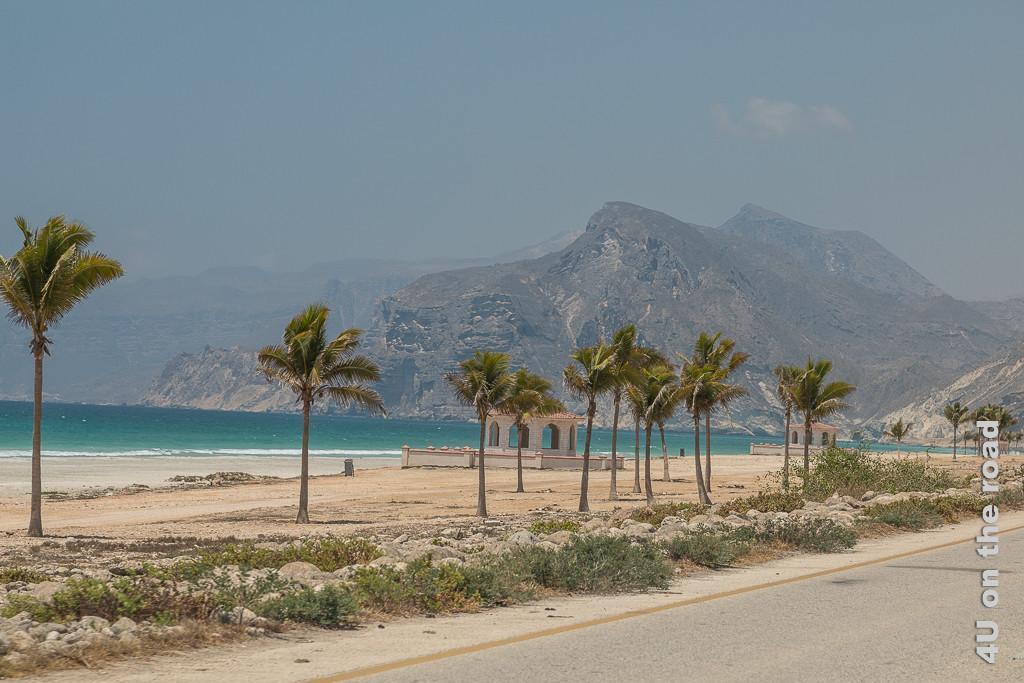 Bild Der Mughsail Beach mit Palmen und Picknickplätzen auf Höhe des Fischerdorfes zeigt den hinteren Strandabschnitt. Im Hintergrund erheben sich recht nah die hohen Klippen. Der Himmel ist von Sand gefärbt eher graublau.