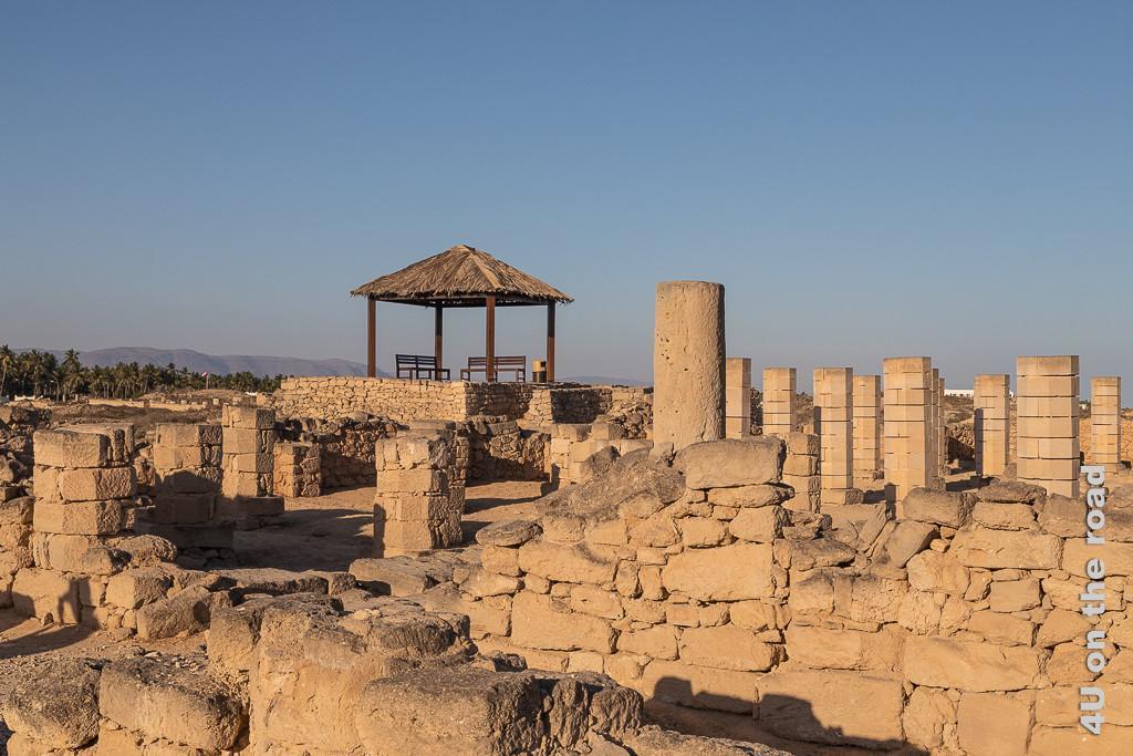 Picknickplatz bei der Grossen Moschee im Al Baleed Archäologiepark zeigt einen Teil der Mauerreste und Säulen der Moschee und im Hintergrund den beschatteten Picknickplatz in Mitten der Ausgrabungsstelle
