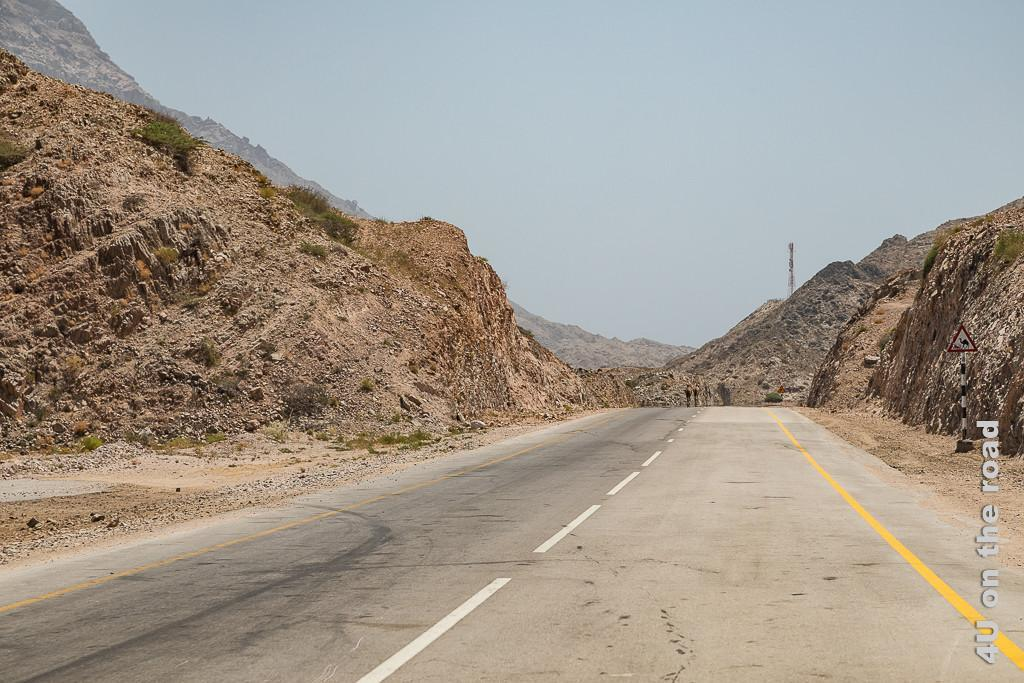 Bild Kamele auf der Strasse zeigt die in die Felsen geschnittene Strasse auf der kaum hinter dem Achtung Kamele Schild auch schon Kamele langlaufen.