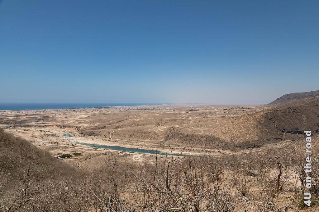 Von oben gesehen Wadi Darbat und die Küste nach dem Wasserfall zeigt die hellbraune zur Küste hin abfallende Landschaft, das türkisfarbene Wasser und das Meer, welches mit dem Horizont verschmilzt.