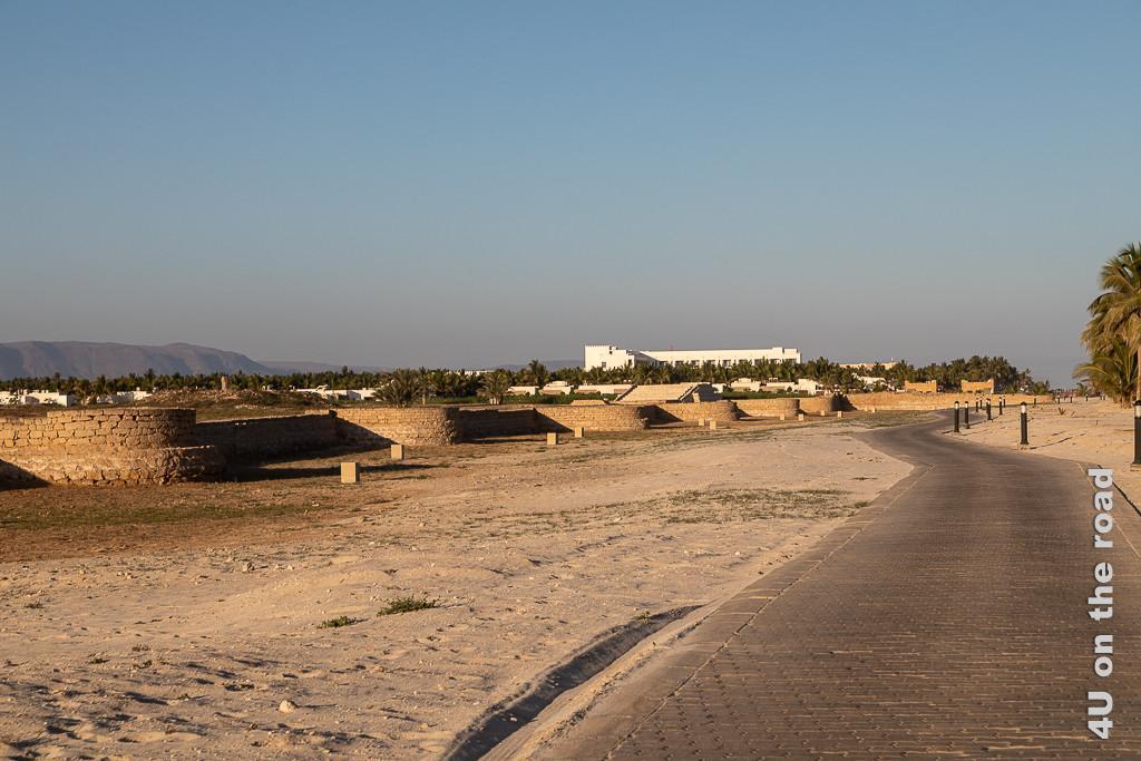 Reste der Stadtmauer am Hafen mit Wellenbrechern, Schiffsanlegern und Wachturm - Al Baleed Archäologiepark