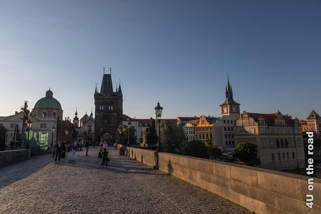 Bild Auf der Karlsbrücke im Morgenlicht zeigt einen Teil der Karlsbrücke mit dem Brückenturm auf der Kleinseite Prags. Auf der Brücke posiert schemenhaft ein Brautpaar.