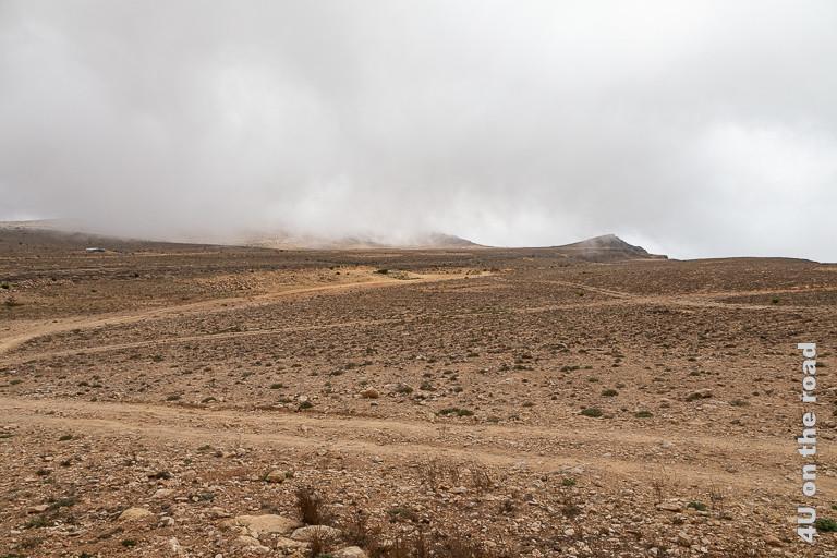 Bild Mit dem Auto auf dem Weg zum Jebel Samhan zeigt wie Wolken von unten über die Klippen hereinziehen und sich über den Hang legen.