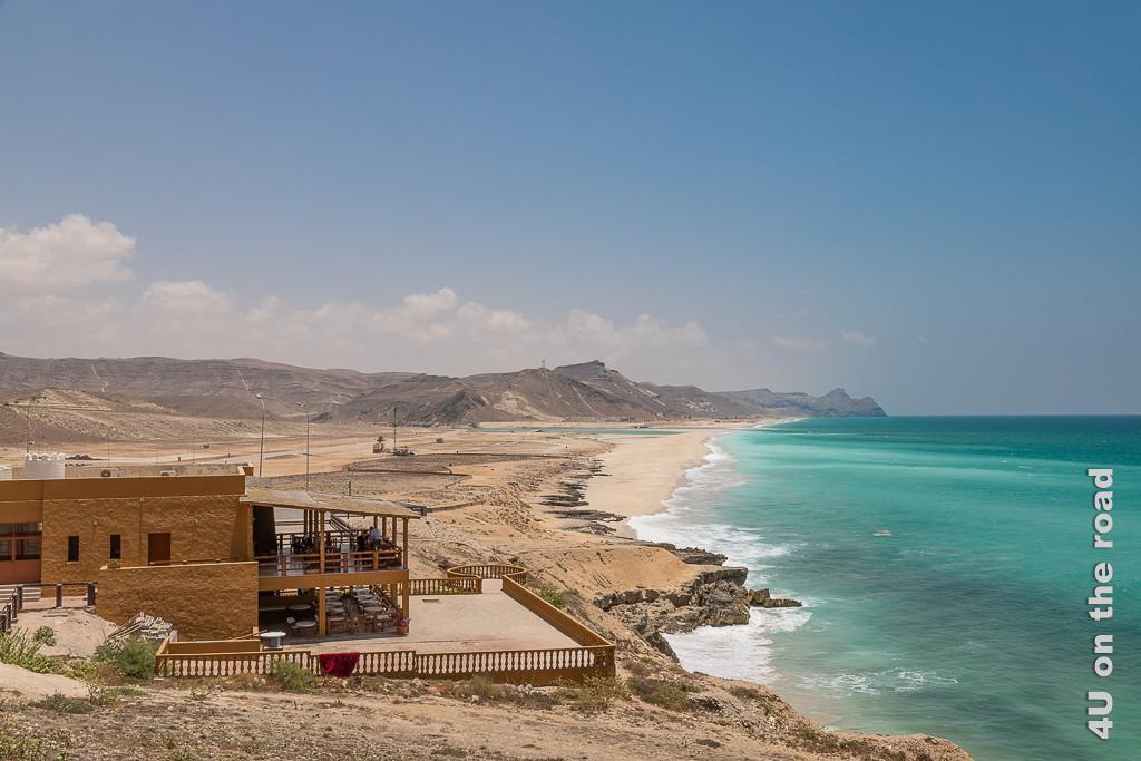 Bild Restaurant an den Blowholes zeigt das Restaurant mit zwei überdachten Schattenterrassen zum Meer hin und den endlos langen Mughsail Beach an den das türkisblaue Meer schäumend anbrandet. Im Hintergrund die Küstenberge.