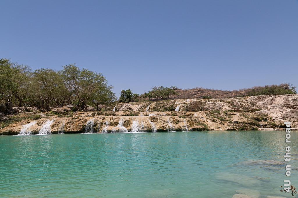 Bild Kleine Wasserfälle in der Trockenzeit zeigt Kalksteinterrassen über die an mehreren Stellen Wasser zur darunter liegenden Terrasse strömt. auf den Felsen wachsen Bäume.