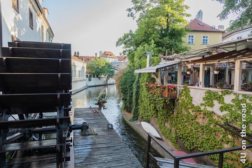 Bild Wasserrad am Teufelsbach zeigt einen schmalen Fluss mit grossem Wasserrad und Restaurant.