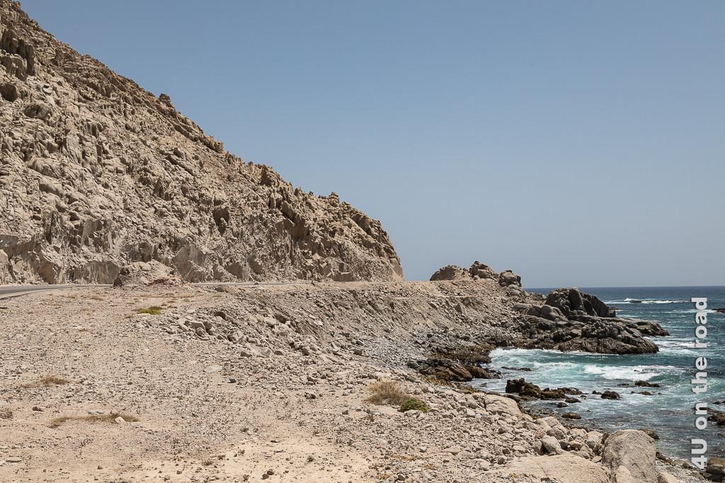 Bild Was wohl hinter der Kurve auf uns wartet? zeigt Felsen, Meer und eine Strasse, die scheinbar ins Nichts abbiegt.