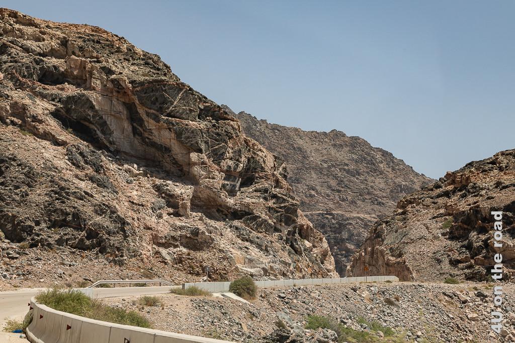 Bild Quarzadern schneiden durch den Fels zeigt schwarze bis rotbraune Felsen, die von von rotbraunen Adern durchschnitten werden.