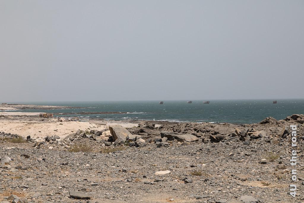 Bild Daus im Dunst zeigt vier auf dem Meer liegende Daus. Im Vordergrund wechseln sich grosse Steine mit Sand ab.