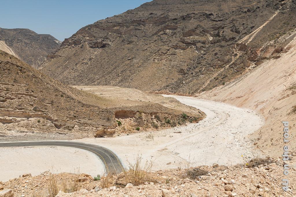 Bild Die Zickzackroad, Oman wird am Tiefpunkt durch das Wadi geführt zeigt das weisse Wadi im Kontrast zu den ockerfarben bis schwarzen Felsen.