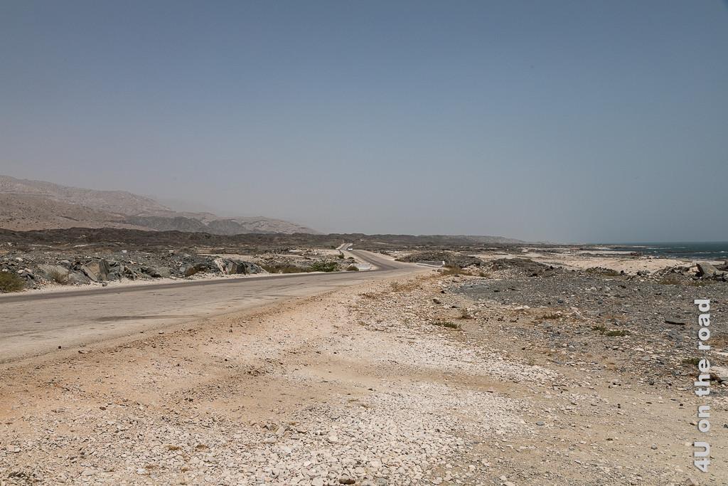 Bild Plötzlich Weite zeigt einen breiten ebenen Streifen zwischen Meer und Felsen durch die Strasse bis zum Horizont führt.