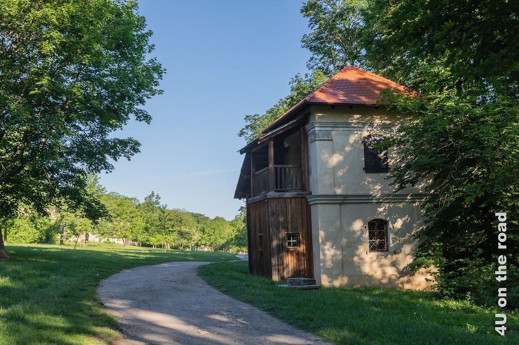 Bild Vom Petrin zum Kloster Strahov, Prag zeigt den sich durch Wiesen und Walnussbäumen schlängelnden Weg. Im Vordergrun steht ein altes Haus mit Holzanbau.